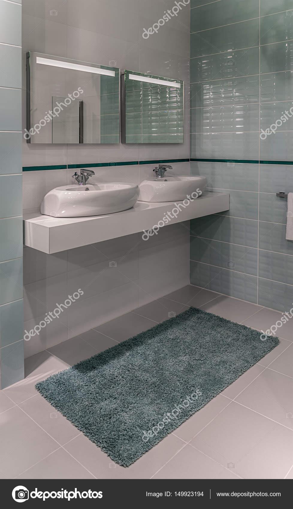 Dos lavabos, espejos y una alfombra en el cuarto de aseo con ...