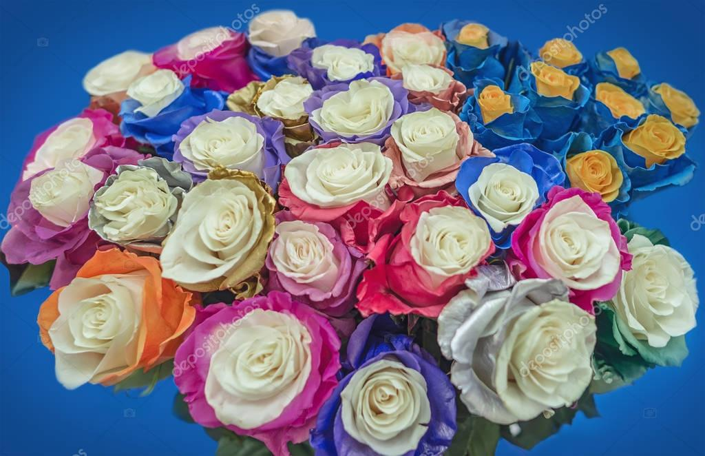 Large bouquet of unusual roses. The flowers chameleons with the silver, gold, bronze, green, orange, blue, pink and red petals on the blue background