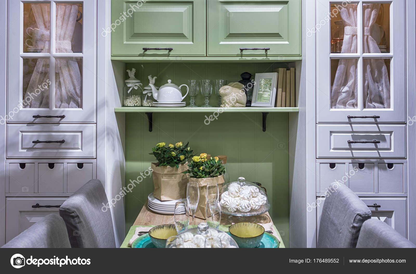 Gemütliche Küche im Stil der Provence. Ein Schrank mit Glastüren und ...