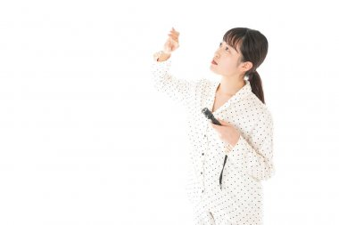 Asian young woman in pajamas with flashlight isolated on a white background