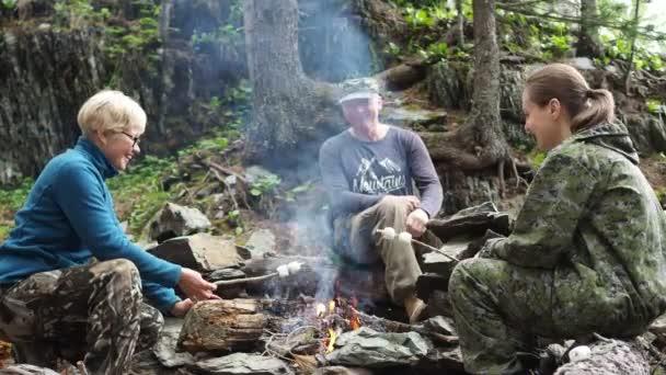 Dobrodružství v přírodě.Dvě šťastné ženy a muž u táboráku v horách připravují marshmallow. Sibiř.