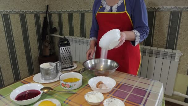 Simple food, pie making. A woman standing in front of the table pours sugar into a bowl with broken eggs. Siberia.
