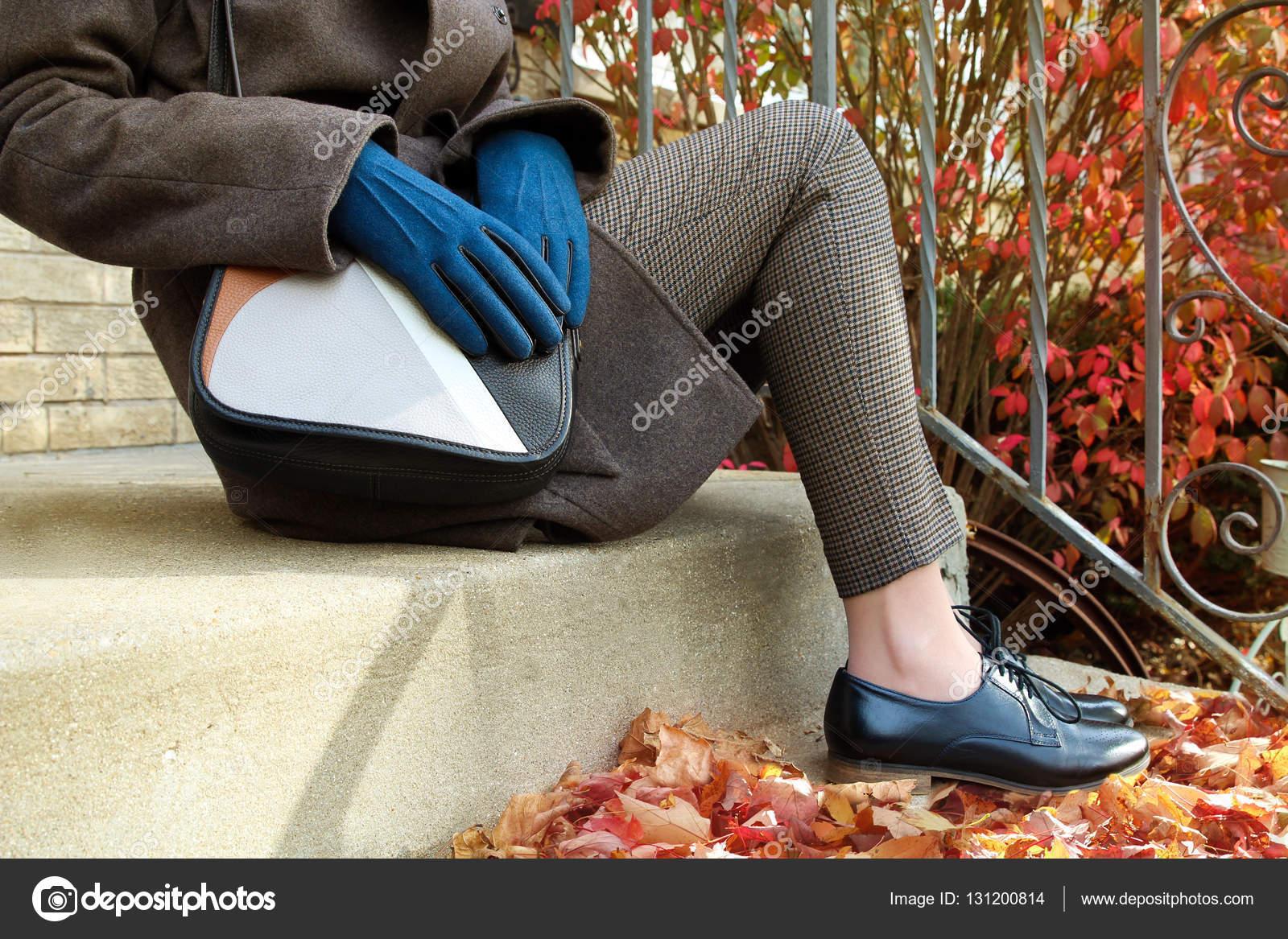 Donna elegante che si siede sulle scale in un cappotto di lana con borsa in  pelle e scarpe moderne classiche nere– immagine stock 1de88d5449c