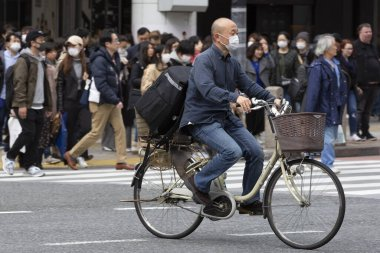 Tokyo, Japan, February 22, 2020 - A man wearing surgical mask to prevent infectious deseases rides a bicycle around Shibuya's famous scramble crossing. Japan has confrimed coronavirus infections cases in the country.