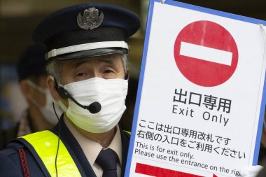 Tokyo, Japan, February 22, 2020 - A member of staff of Shibuya Station wearing surgical mask to prevent infectious deseases holds a sign at the exit of the station. Japan has confrimed coronavirus infections cases in the country.