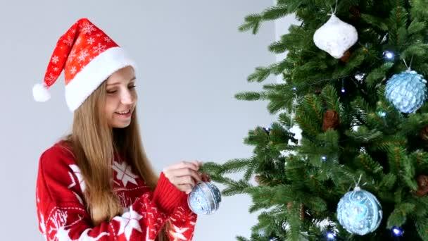 Happy Woman in Santa Hat Díszíteni karácsonyfa, koncepció az újévi ünnepek
