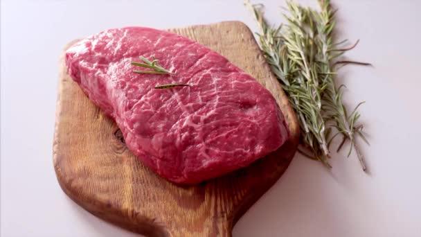 Close Up of raw čerstvý steak podávaný s rozmarýnem na rustikální dřevěné desce