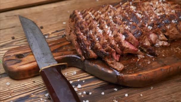 Szeletelt grillezett húsmarha steak Ribeye fűszerekkel rusztikus fa vágódeszka