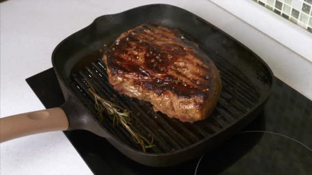 Man Hands odstraňuje grilované hovězí steak se solí na grilu Pan na kuchyni
