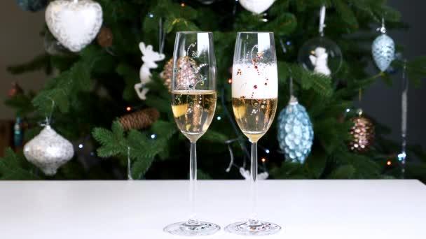 Dvě sklenice šampaňského na pozadí vánoční stromeček