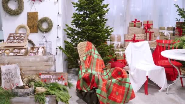 Pokoj s vánoční výzdobou, dárkové krabice, vánoční stromky a houpací židle