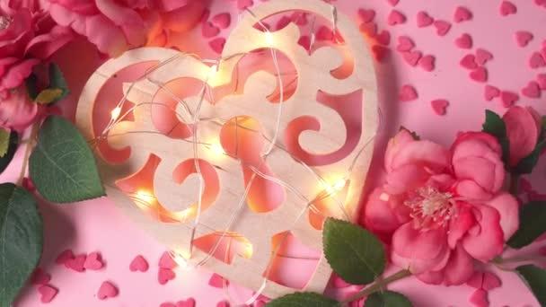 Holzherz mit Lichterkranz liegt auf rosa Hintergrund mit Herzen und Blumen