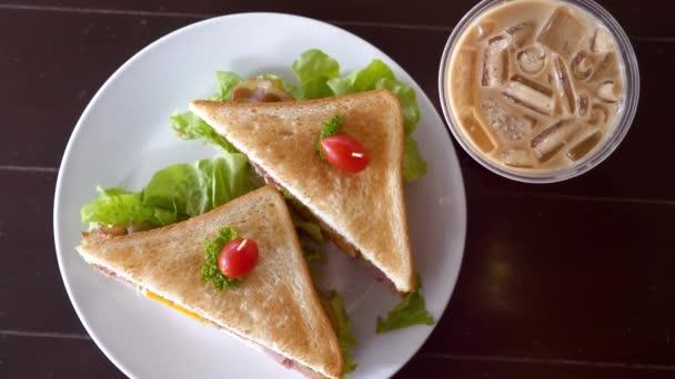 Draufsicht auf Sandwiches auf weißem Teller und Eiskaffee auf dem Tisch im Cafe