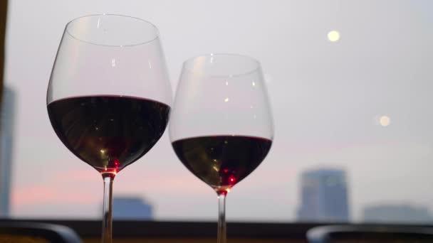 Dvě sklenice červeného vína stojan na stole s Evening City na pozadí