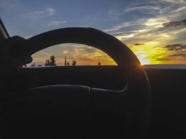 Driving on a highway at sunset