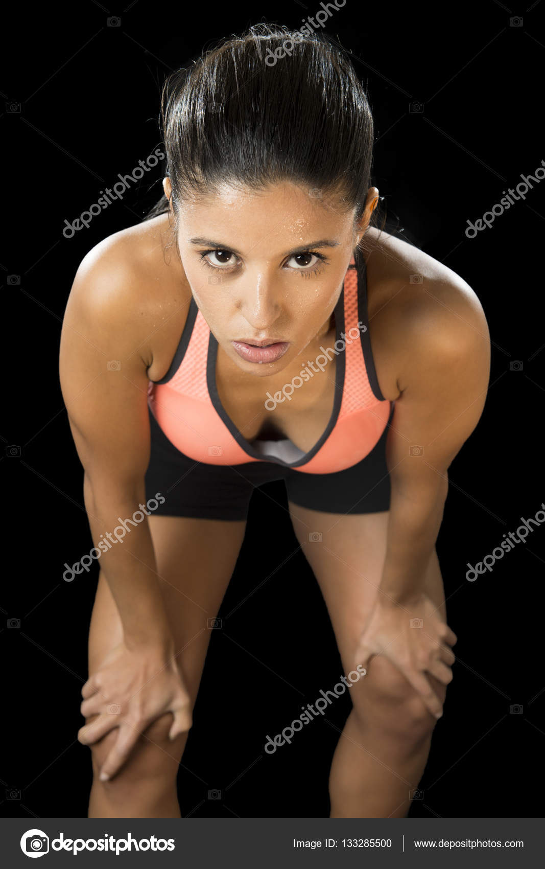 09be7b7601034 Young attractive sexy latin sport woman posing in fierce and badass face  expression with fit slim body isolated on black background in healthy  lifestyle and ...