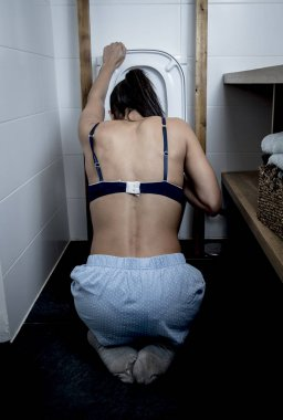 back view of bulimic woman feeling sick vomiting and throwing up in WC toilet