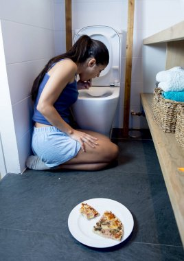 woman vomiting and throwing up kneeling on floor of toilet WC guilty after eating pizza