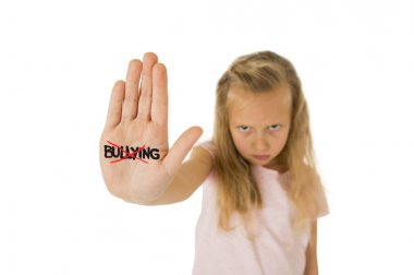 sweet and scared little schoolgirl showing the word bullying scratched written in her hand
