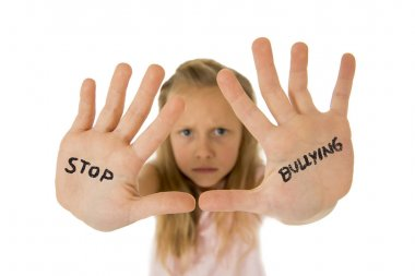 sweet and scared little schoolgirl showing the text stop bullying written in her hands