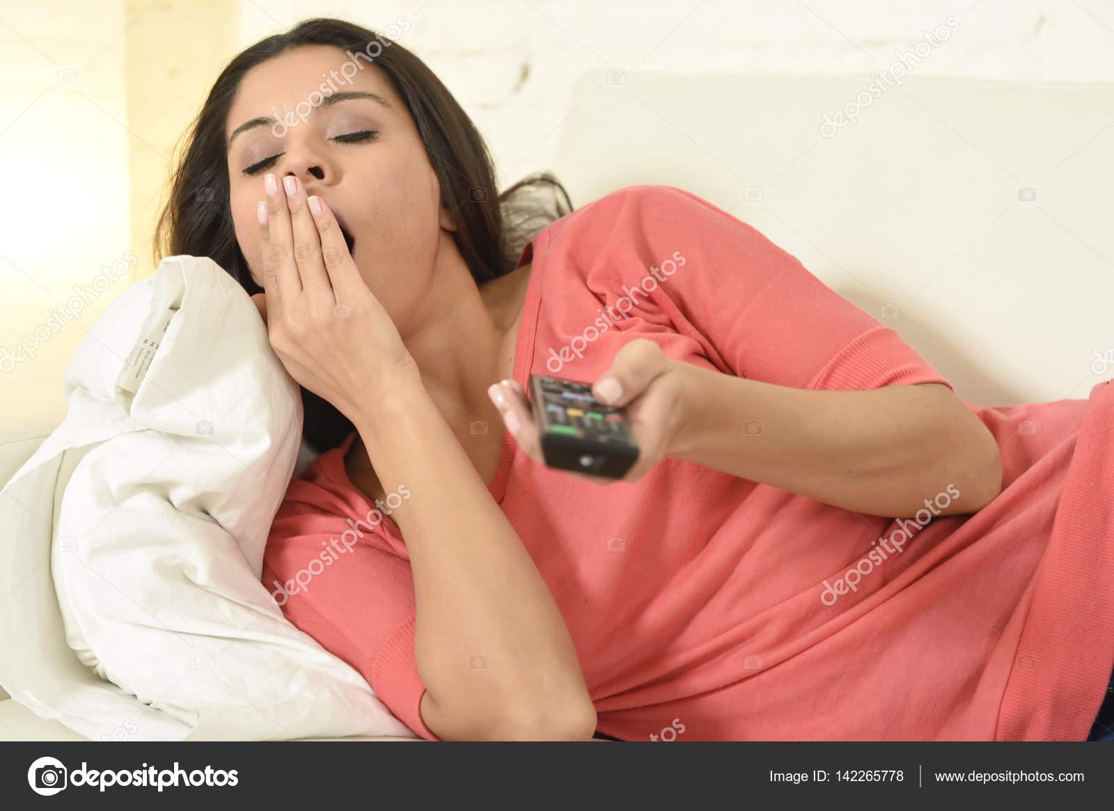 junge schöne spanische Frau zu Hause vor dem Fernseher müde und ...
