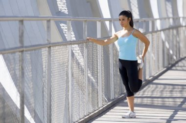 young beautiful athletic sport woman stretching after running crossing modern metal city bridge