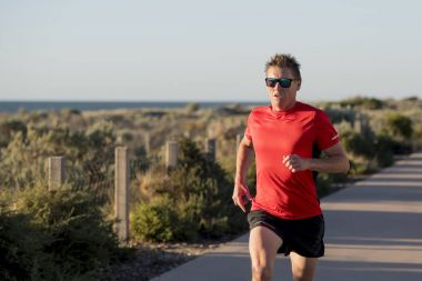 young attractive and happy sport runner man with fit and strong healthy body training on off road track in Summer running workout