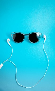 beautiful sunglasses on blue background with earphones