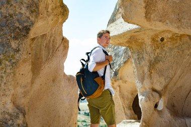 Young man traveling in Capadocia exploring Uchisar Castle.