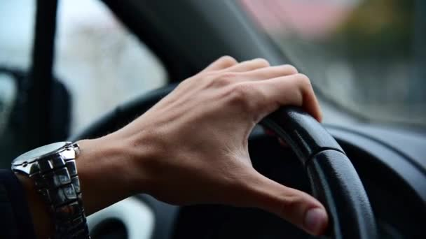 Handled video of man's hand with wristwatch on steering wheel.