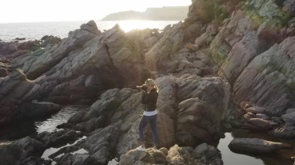Női fotós Dslr fényképezőgép fotózás üres strandon naplemente alatt.