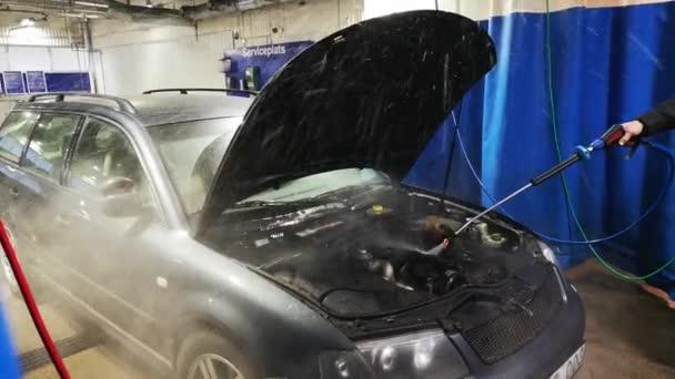 Self service car wash. Man washing his car at automobile washing station. Cleaning Engine Car Using High Pressure Water.