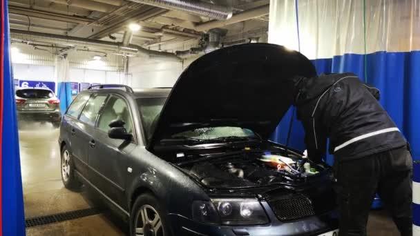 Samoobslužná myčka aut, muž si myje auto u myčky aut. Čištění motoru auto pomocí vysokotlaké vody.