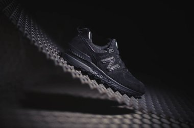 Black New Balance 574 sneakers shot outdoor on dark industrial background. Illustrative editorial close up photo of casual sport shoes shot in Krasnoyarsk, Russia - January 9, 2018