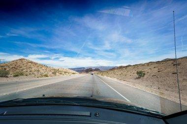 Open road in desert as seen through car windscreen