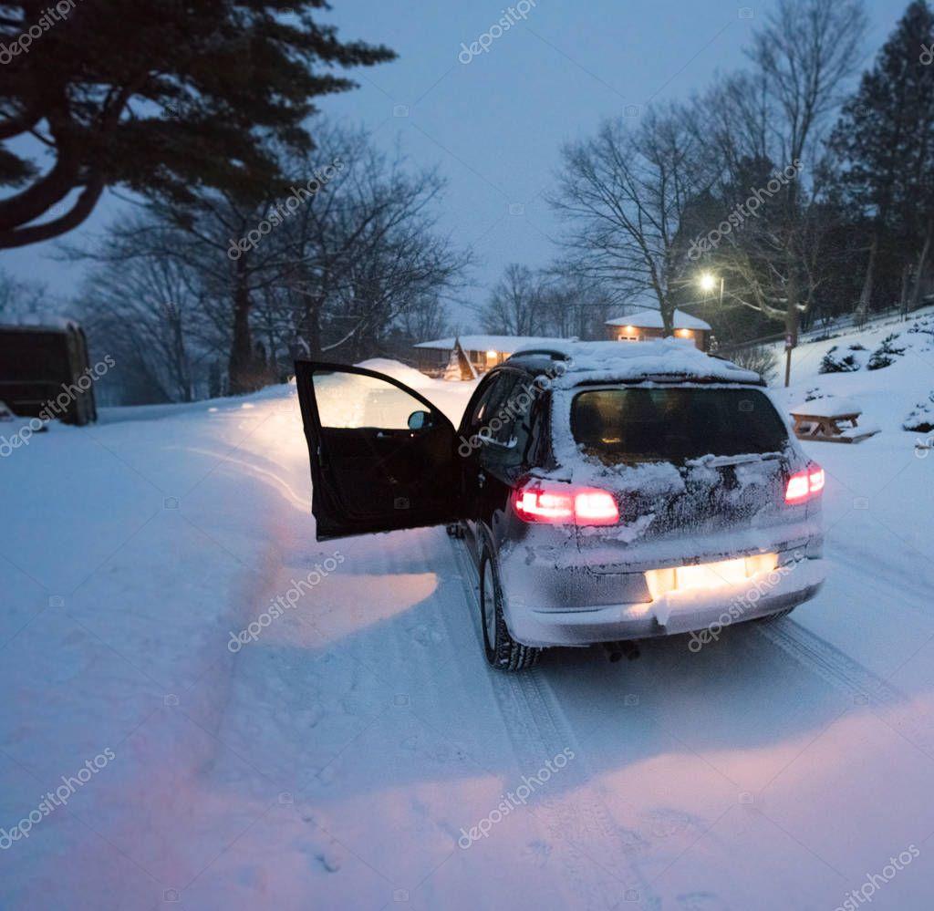 Car in snow at dusk, drivers door open, rear lights illuminate