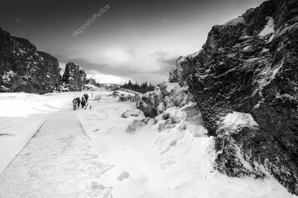 Small group of people walking on snow covered pathway