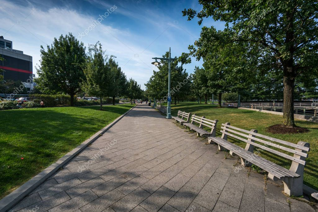 Footpath and empty benches in park with paving slabs