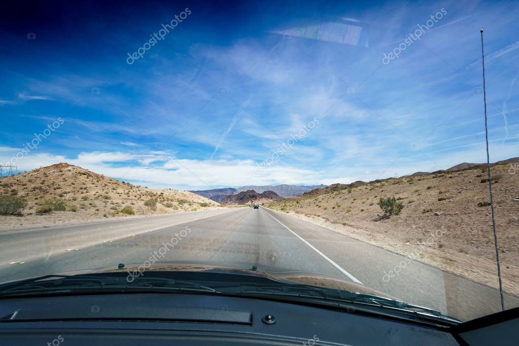 Open road in desert as seen through car windscreen