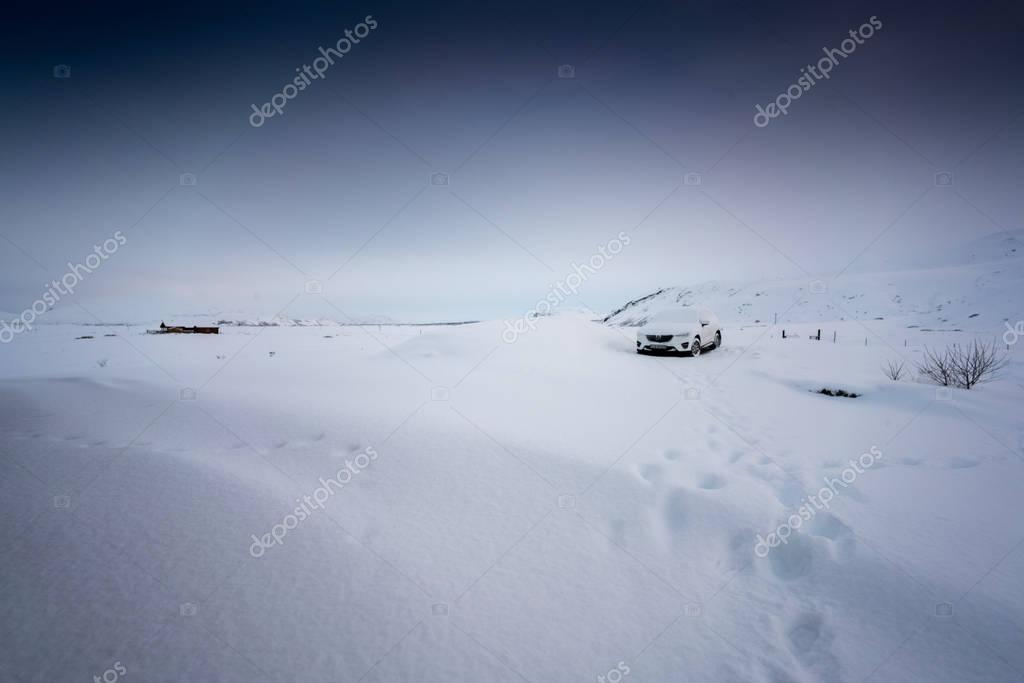 Deep snow covered car and landscape