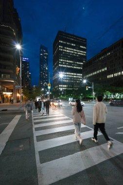 People crossing city street of Toronto, Canada