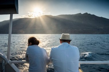 Couple admiring scenic view of sea and mountain from boat, Crete, Greece