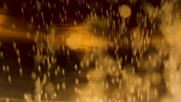 Pohyb zlatých bublin ve vodě