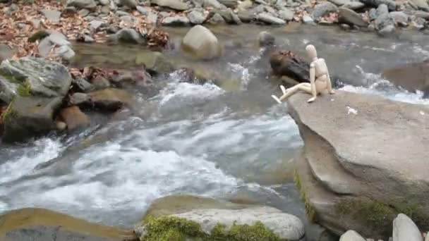 Articulated little man sits on a stone above a mountain river