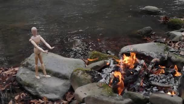 Kloubový mužík se ohřeje u ohně na břehu horské řeky