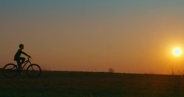 Chlapec jede na kole po cestě při západu slunce. Natáčím zezadu. 4K