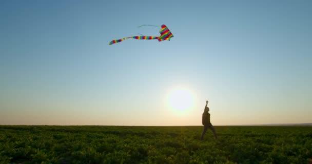 Chlapec si hraje s drakem na obloze při západu slunce. 4K
