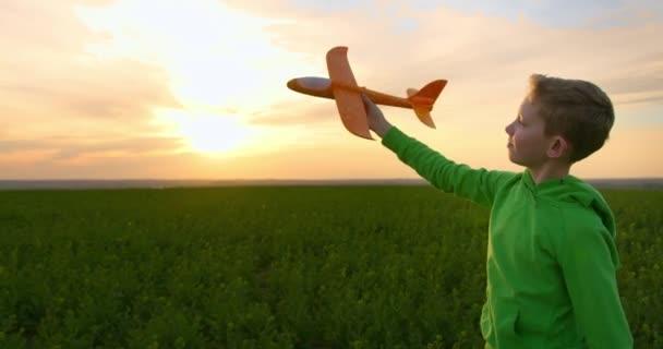Chlapec s letadlem na hraní v ruce jde přes pole. Procházka přírodou. Západ slunce. 4K