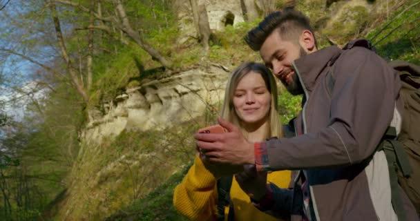 Záběr zblízka. Chlap a holka se dívají na mapu na svém smartphonu. Pěší túra v lese. 4k