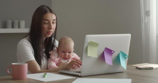 Az anya egy laptopon dolgozik. A baba egy játékkal játszik. 4K